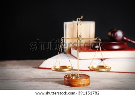 Justice scales with wooden gavel and books on black background - stock photo
