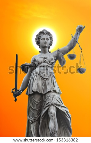 justice statue with sword and scale. sun and orange sky in the background. - stock photo