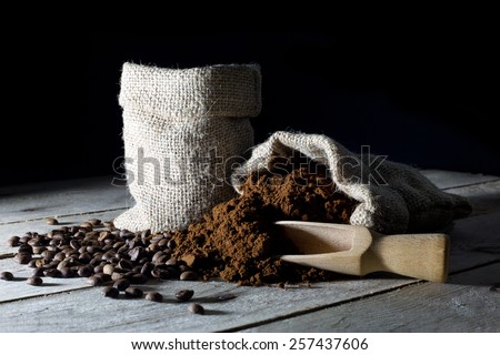 Jute Bags Filled with Ground Coffee and Coffee Beans on an Old Rustic Wooden Table , Black Background - stock photo
