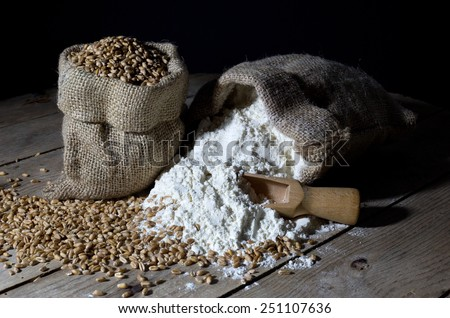 Jute Bags Filled with Wheat and Flour on an Old Wooden Table Over Black Background - stock photo