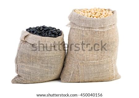Jute sacks with soja beans and black legume isolated on white background - stock photo