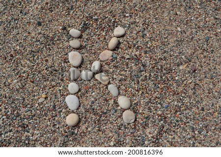K letter made of stones on sand - stock photo