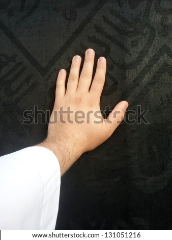 Kaaba Mecca in Saudi Arabia and Muslim pilgrims coming for Hajj, male hand touching the black Cover - stock photo