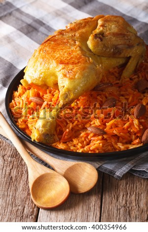 Kabsa - spicy rice with vegetables and chicken on a plate close-up. vertical