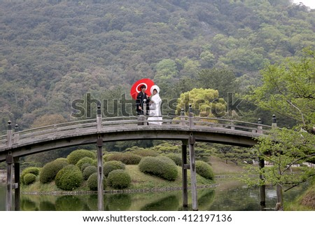 KAGAWA, JAPAN - APRIL 10, 2016 : Japanese wedding couple dressed in traditional kimono are standing wooden brige at Japanese garden (Riturin Park). - stock photo