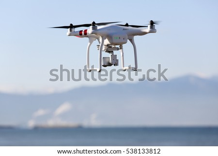 KAGAWA, JAPAN - DECEMBER 15, 2016: White remote controlled Drone Dji Phantom 3 equipped with high resolution video camera hovering in air with beach and clear blue sky