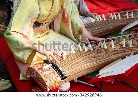 KAGAWA, JAPAN - NOVEMBER 22: Japanese women dressed in traditional kimono clothing playing the koto (Japanese traditional instrument). November 22, 2015 in Kagawa, Japan. - stock photo