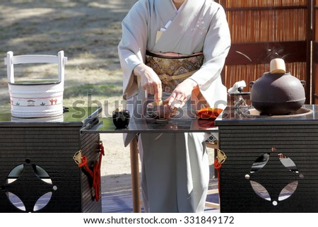 KAGAWA, JAPAN - OCTOBER 25, 2015: Japanese woman in traditional kimono prepares the tea ceremony at garden of the Marugame-castle on October 25, 2015 in Kagawa Japan. - stock photo