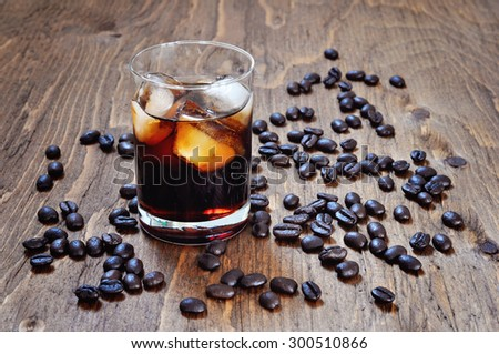 Kahlua liqueur in shot glass with coffee beans on a wooden table, selective focus - stock photo