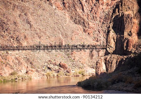Kaibab Bridge with tourists riding mules in Grand Canyon. - stock photo