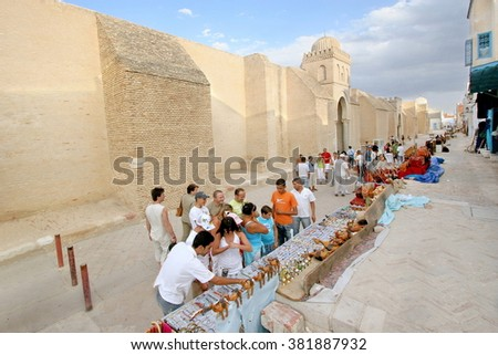 KAIROUAN, TUNISIA - September 05, 2007:  The crowded street market next to the medieval citadel walls of Medina.