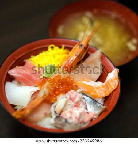 Kaisendon, a bowl of boiled rice topped assorted seasonal raw seafood sashimi including whole prawn, leg meat of snow crab, salmon roe, and various fish (a variant of Donburi) - stock photo