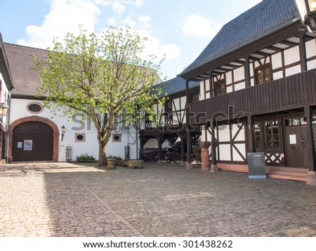Kaiserslautern, Germany - April 18, 2015: Theodor-Zink-Museum, Garden inside the museum with old carriage used as a hearse. The house is plastered and painted white very bright - stock photo