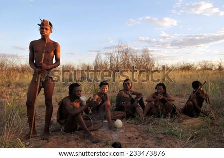 KALAHARI, BOTSWANA - DECEMBER 31, 2008: group of bushmen in the desert making fire - stock photo
