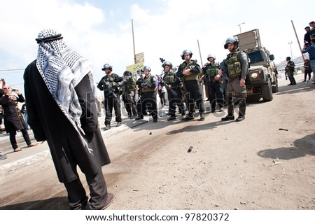 KALANDIA, OCCUPIED PALESTINIAN TERRITORIES - MARCH 8: A Palestinian man confronts Israeli soldiers at Kalandia checkpoint during demonstrations on March 8, 2012. - stock photo