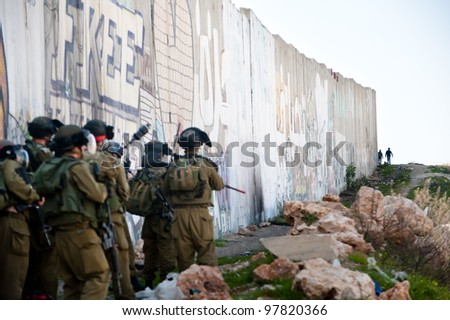 KALANDIA, OCCUPIED PALESTINIAN TERRITORIES - MARCH 8: Heavily armed Israeli soldiers eye Palestinian youths during protests against the occupation of Palestine on March 8, 2012 in Kalandia - stock photo