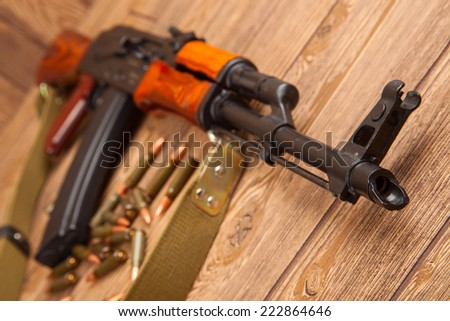Kalashnikov assault rifles with ammunition on a wooden table