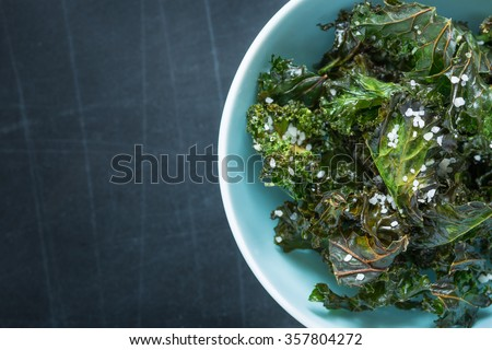 Kale chips with salt in pastel blue bowl captured from above (top view). Healthy dietetic snack. Black chalkboard as background. Background layout with free text space. - stock photo