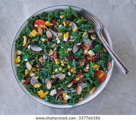 Kale salad, chopped kale, grilled corn, tomatoes, dried cranberries and nuts in a bowl on stone background - stock photo