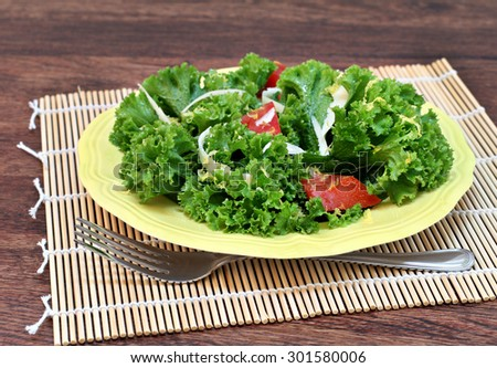 Kale salad with tomato, parmesan shreds, lemon zest and sea salt.  Selective focus on foreground of salad. - stock photo