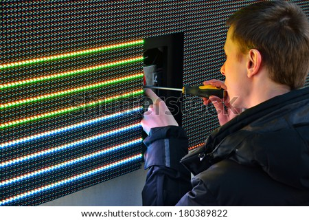 KALININGRAD, RUSSIA - MARCH 7, 2014: Electrician repair the damaged item in large advertising LED screen on the street - stock photo
