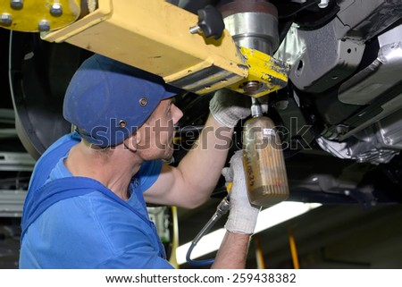 KALININGRAD, RUSSIA - SEPTEMBER 16, 2014: The worker fixes a detail to the car bottom. Assembly conveyor of automobile plant