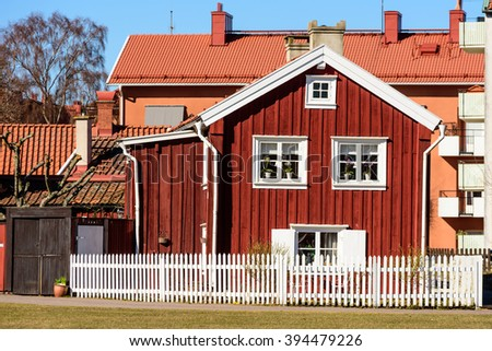 Kalmar, Sweden - March 17, 2016: An old red wooden house in the middle of the city, with modern buildings in the background. White fence in front of house.