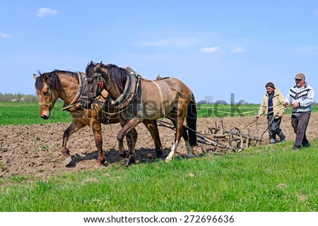 Kalush, Ukraine- April 24: Farmers work on a field using a manual plow on horse-drawn  near the town Kalush, Western Ukraine on April 24, 2015 - stock photo
