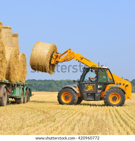 Kalush, Ukraine - August 14: Loading bales of straw on the car in the field near the town Kalush, Western Ukraine August 14, 2015