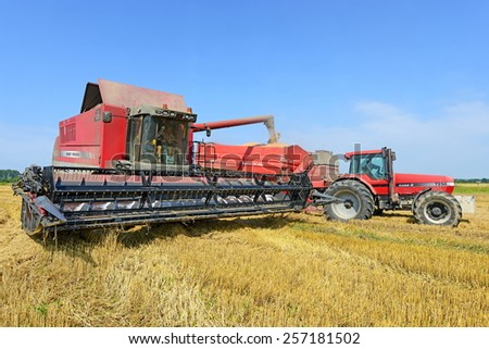 Kalush, Ukraine - August 10 : Modern  combine harvesting grain in the field near the town Kalush August 10, 2014 - stock photo