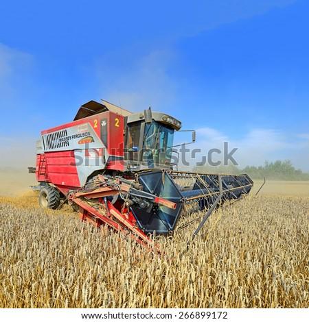 Kalush, Ukraine - AUGUST 10: Modern  combine harvesting grain in the field near the town Kalush, Western Ukraine August 10, 2014  - stock photo