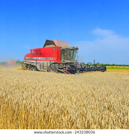 Kalush, Ukraine - August 4: Modern John Deere combine harvesting grain in the field near the town Kalush, Western Ukraine August 4, 2014 - stock photo