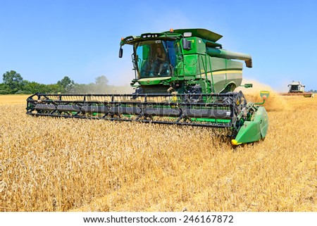 Kalush, Ukraine - AUGUST 11: Modern John Deere combine harvesting grain in the field near the town Kalush, Western Ukraine August 11, 2014  - stock photo
