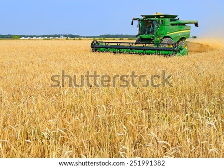 Kalush, Ukraine - AUGUST 7: Modern John Deere combine harvesting grain in the field near the town Kalush, Western Ukraine August 7, 2013  - stock photo