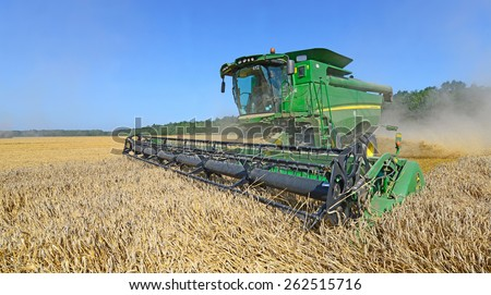 Kalush, Ukraine -  August 11 Modern John Deere combine harvesting grain in the field near the town Kalush, Western Ukraine August 11, 2014  - stock photo