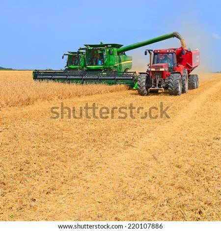 Kalush, Ukraine - AUGUST 7: Modern John Deere combines harvesting grain in the field near the town Kalush, Western Ukraine August 7, 2013  - stock photo