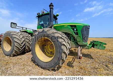 Kalush, Ukraine - August 10 :Modern John Deere tractor in the field near the town Kalush, August 10, 2014 - stock photo