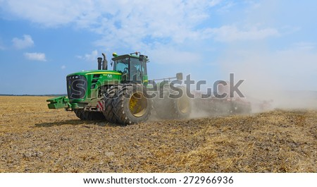 Kalush, Ukraine - August 10 : The modern John Deere tractor performs sowing cereals trailed planter in the field near the town of Kalush, Western Ukraine on August 10, 2014 - stock photo