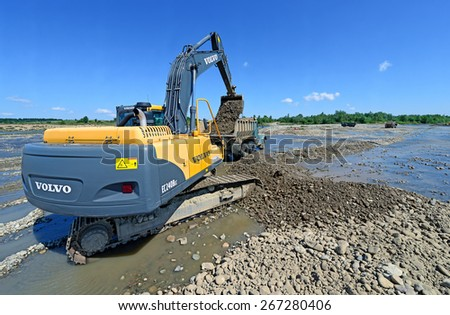 Kalush, Ukraine - July 22: Extracting and loading gravel excavated in the mainstream of the river near the town Kalush, Western Ukraine July 22, 2013 - stock photo