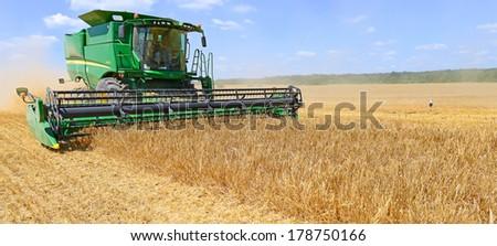 Kalush, Ukraine - July 9: Modern John Deere combine harvesting grain in the field near the town Kalush, Western Ukraine July 9, 2013 - stock photo