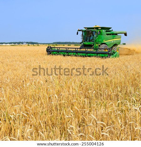 Kalush, Ukraine - July 9: Modern John Deere combine harvesting grain in the field near the town Kalush, Western Ukraine July 9, 20133  - stock photo