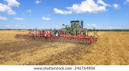 Kalush, Ukraine - July 9: Modern John Deere tractor on soil treated cultivator in the field near the town Kalush, Western Ukraine July 9, 2013 - stock photo