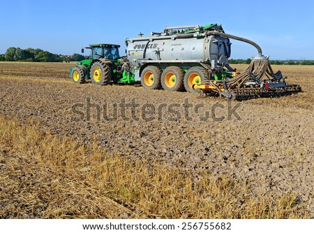 Kalush, Ukraine - July 9: Modern John Deere tractor with a set of equipment for making liquid fertilizer into the soil in the field near the town Kalush, Western Ukraine July 9, 2013 - stock photo