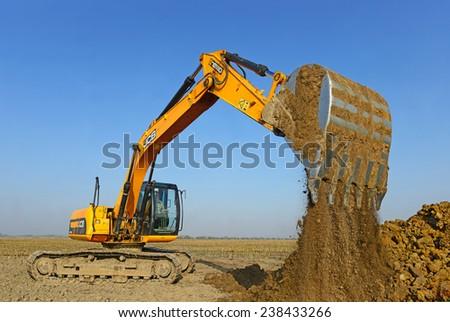 Kalush, Ukraine October 14: Modern JCB excavator on the highway pipeline performs excavation work in the field near the town Kalush, Western Ukraine October 14, 2014 - stock photo