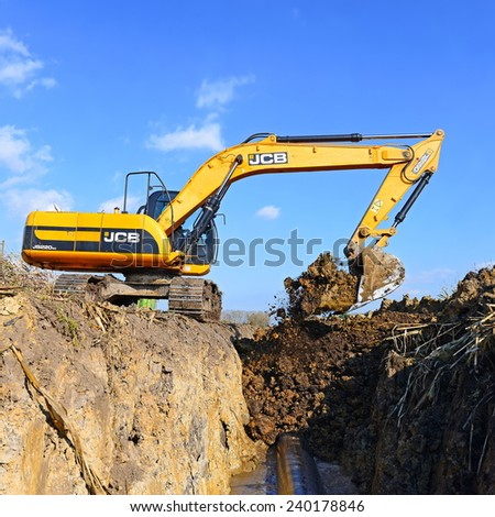 Kalush, Ukraine October 7: Modern JCB excavator on the highway pipeline performs excavation work in the field near the town Kalush, Western Ukraine October 7, 2014 - stock photo