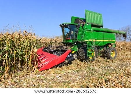 Kalush, Ukraine � OCTOBER 14: Modern John Deere combine harvesting corn  in the field near the town Kalush, Western Ukraine October 14, 2014 - stock photo