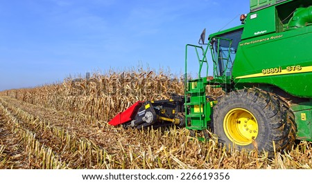 Kalush, Ukraine - OCTOBER 8: Modern John Deere combine harvesting corn  in the field near the town Kalush, Western Ukraine October 8, 2013 - stock photo