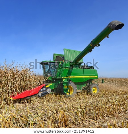 Kalush, Ukraine -OCTOBER 8: Modern John Deere combine harvesting corn  in the field near the town Kalush, Western Ukraine October 8, 2013 - stock photo