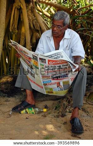 KALUTARA, SRI LANKA - DECEMBER 23, 2008: A middle-aged man reads a newspaper in the morning after the last night booze - stock photo