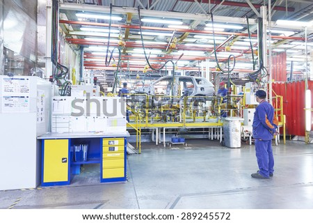 KALUZHSKY region, RUSSIA - JUNE 16: Worker watching other workers assembling Mitsubishi Outlander body at automotive Mitsubishi (PCMA) plant on june 16, 2015 - stock photo